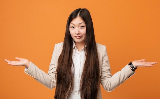 Junge chinesische geschäftsfrau, die ihn schultern in fragender geste bezweifelt und zuckt.