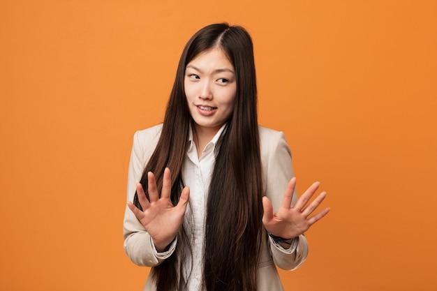 Junge chinesische geschäftsfrau, die jemand zeigt eine geste des ekels zurückweist.