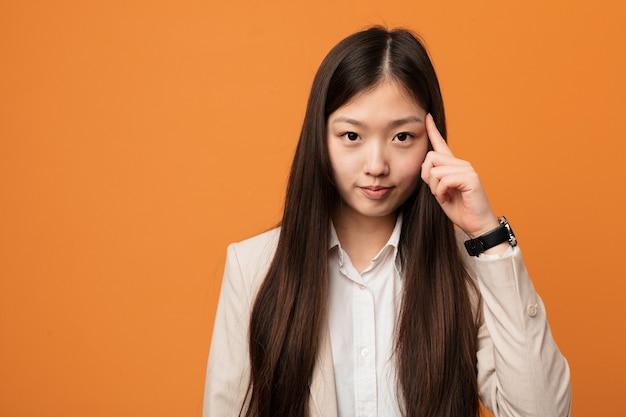 Junge chinesische geschäftsfrau, die tempel mit dem finger, denkend zeigt, konzentrierte sich auf eine aufgabe.
