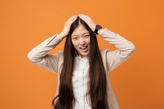 Junge chinesische geschäftsfrau lacht froh, hände auf kopf halten. glück-konzept.