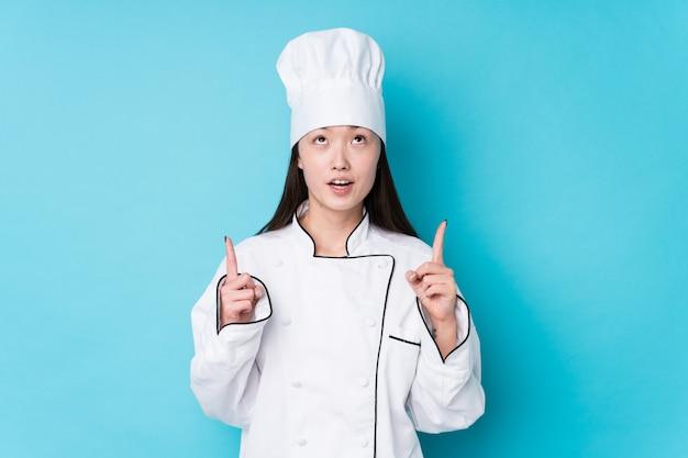 Junge chinesische kochfrau lokalisiert, die oben mit geöffnetem mund zeigt.