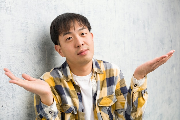 Junge chinesische manngesichtsnahaufnahme, die schultern zweifelt und zuckt