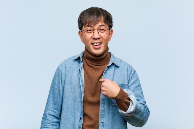 Junge chinesische mannperson, die von hand auf eine leere stelle des hemdes zeigt, stolz und zuversichtlich