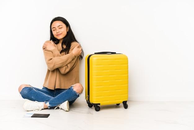 Junge chinesische reisende frau, die auf dem boden mit den isolierten umarmungen eines koffers sitzt, sorglos lächelnd und glücklich.