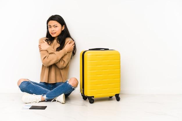 Junge chinesische reisende frau, die auf dem boden mit einem isolierten koffer sitzt, der wegen niedriger temperatur oder einer krankheit kalt wird.