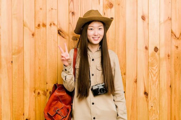 Junge chinesische reisende frau, die siegeszeichen zeigt und breit lächelt.