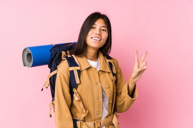 Junge chinesische reisende frau freudig und sorglos, ein friedenssymbol mit den fingern zeigend.