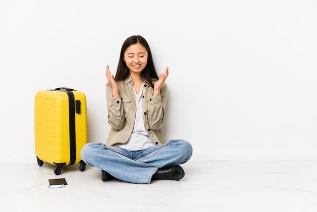 Junge chinesische reisendfrau, die ein internat halten sitzt, überschreitet frohes viel lachen. glück-konzept.