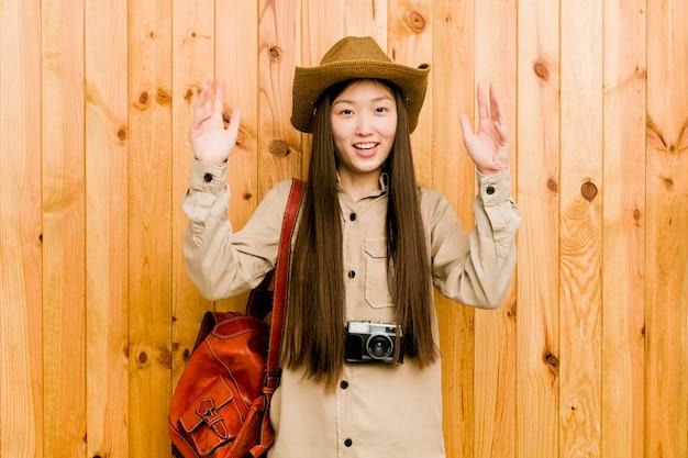 Junge chinesische reisendfrau, die eine angenehme überraschung empfängt, hände aufgeregt und anhebt.