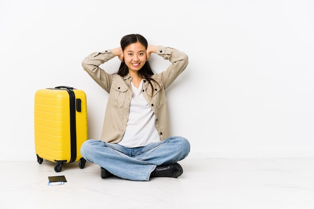 Junge chinesische reisendfrau, die eine bordkarte halten bedeckt ohren mit den händen versucht, nicht zu lauten ton zu hören sitzt.