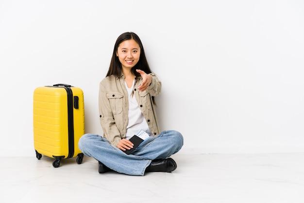 Junge chinesische reisendfrau, die eine bordkarte halten hand an der kamera in der grußgeste ausdehnend sitzt.