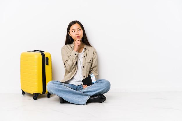 Junge chinesische reisendfrau, die eine bordkarte halten schaut seitlich mit zweifelhaftem und skeptischem ausdruck sitzt.
