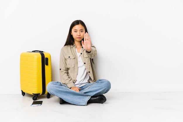 Junge chinesische reisendfrau, die eine bordkarte halten steht mit der ausgestreckten hand zeigt das stoppschild, sie verhindern sitzt.