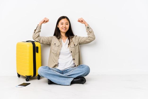 Junge chinesische reisendfrau, die eine bordkarte halten zeigt stärkegeste mit den armen, symbol der weiblichen energie sitzt