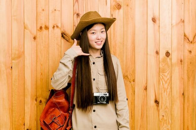 Junge chinesische reisendfrau, die eine handyanrufgeste mit den fingern zeigt.
