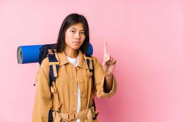 Junge chinesische reisendfrau, die nummer eins mit dem finger zeigt.