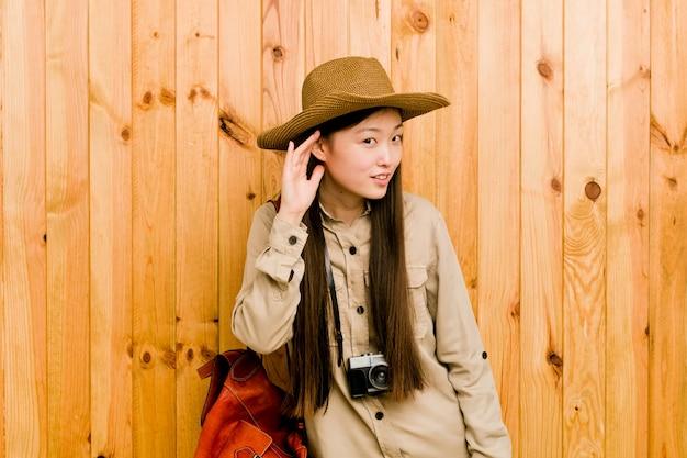 Junge chinesische reisendfrau, die zum hören eines klatsches versucht.