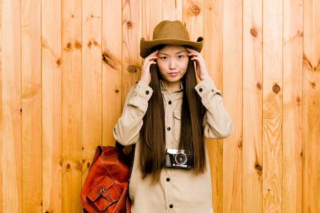 Junge chinesische reisendfrau konzentrierte sich auf eine aufgabe und hielt die zeigefinger, die kopf zeigen.