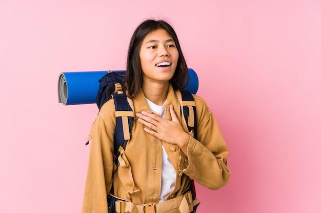 Junge chinesische reisendfrau lacht laut, hand auf kasten halten.