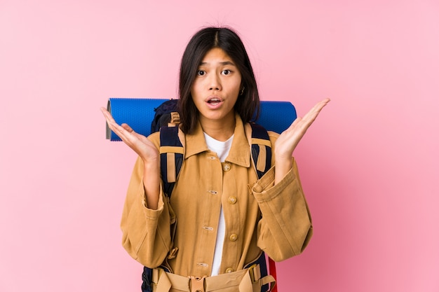 Junge chinesische reisendfrau lokalisiert überrascht und entsetzt.