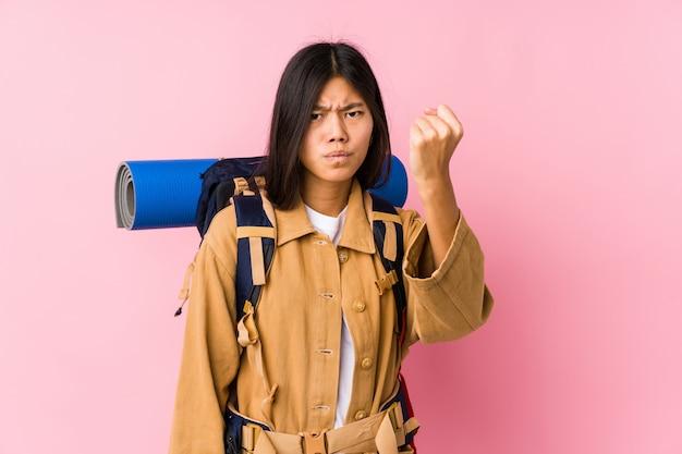 Junge chinesische reisendfrau lokalisierte das zeigen der faust zur kamera, aggressiver gesichtsausdruck.