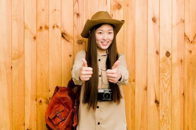 Junge chinesische reisendfrau mit den daumen ups, beifall über etwas, unterstützung und respektkonzept.