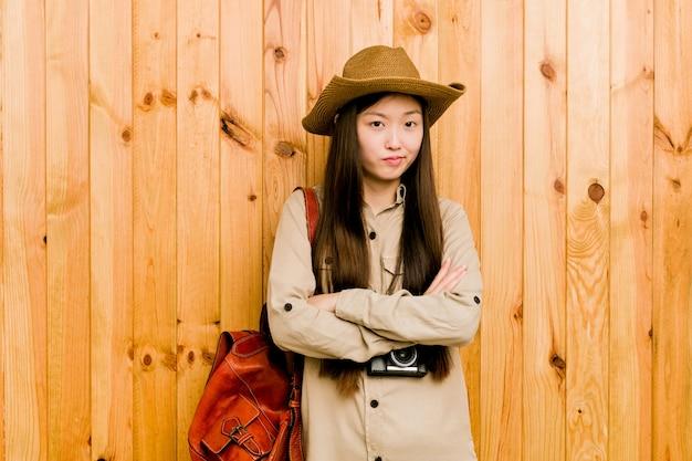 Junge chinesische reisendfrau unglücklich mit sarkastischem ausdruck.