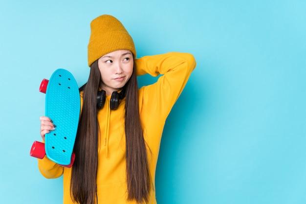 Junge chinesische skaterfrau isoliert, die den hinterkopf berührt, denkt und eine wahl trifft.