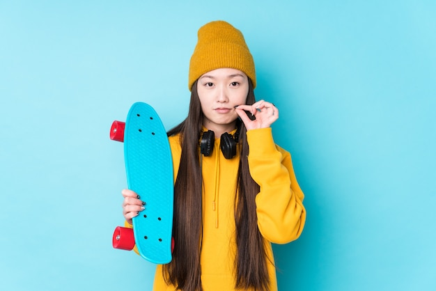 Junge chinesische skaterfrau isoliert mit den fingern auf den lippen, die ein geheimnis halten.