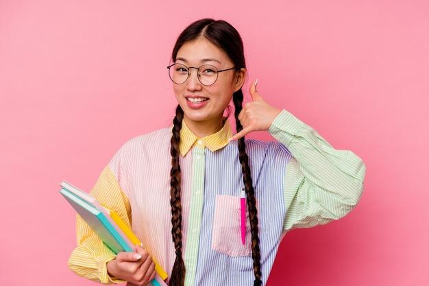 Junge chinesische studentin, die bücher hält, die ein mode-mehrfarbenhemd und -geflecht tragen, lokalisiert auf rosa hintergrund, der eine handy-anrufgeste mit den fingern zeigt.
