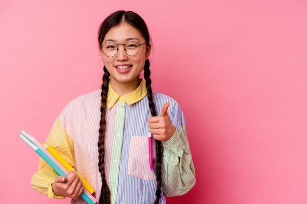 Junge chinesische studentin, die bücher hält, die ein mode-mehrfarbenhemd und -geflecht tragen, lokalisiert auf rosa hintergrund lächelnd und daumen hochheben