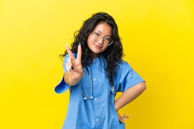Junge chirurg arzt asiatische frau isoliert auf gelbem hintergrund lächelt und zeigt victory-zeichen