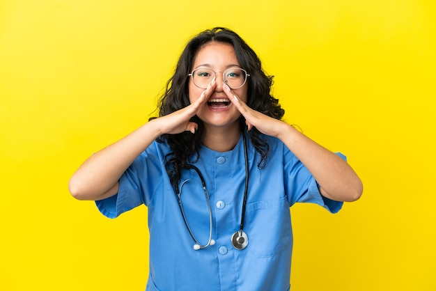 Junge chirurg arzt asiatische frau isoliert auf gelbem hintergrund schreien und etwas ankündigen