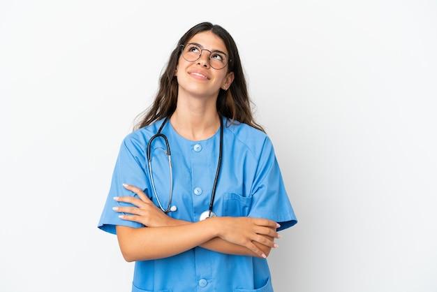 Junge chirurg arzt kaukasische frau isoliert auf weißem hintergrund beim lächeln nachschlagen
