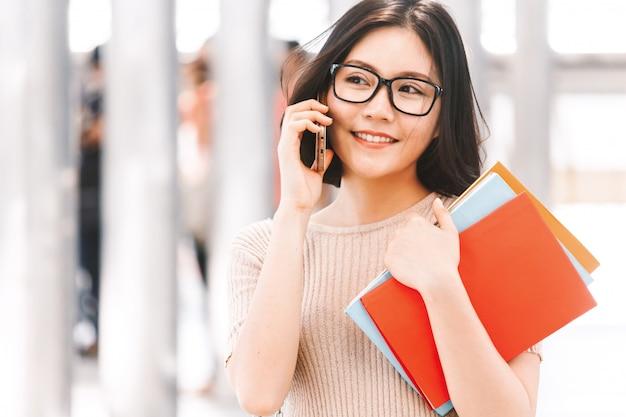 Junge college-frau, die das buch geht und einen smartphone im campus verwendet