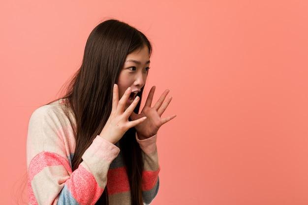 Junge coole chinesische frau schreit laut, hält augen offen und hände angespannt.