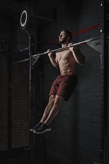 Junge crossfit-athletin macht klimmzüge im fitnessstudio. starker mann beim funktionellen training