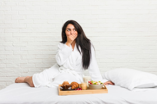 Junge curvy frau, die ein frühstück auf dem bett durchdacht nimmt, schauend zu einem kopienraumbedeckungsmund mit der hand.