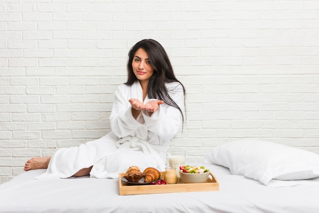 Junge curvy frau, die ein frühstück auf dem bett hält etwas mit den palmen, der kamera anbietend nimmt.