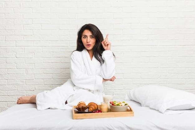 Junge curvy frau, die ein frühstück auf dem bett hat irgendeine großartige idee, von der kreativität nimmt.