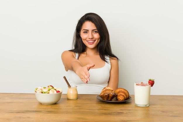 Junge curvy frau, die ein frühstück ausdehnt hand an der kamera in der grußgeste nimmt