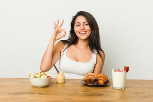 Junge curvy frau, die ein frühstück nett und überzeugt nimmt, okaygeste zeigend.