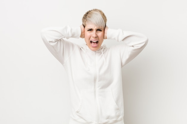 Junge curvy frau, die ein weißes hoodiebedeckungsohren mit den händen versuchen, nicht zu lauten ton zu hören trägt.