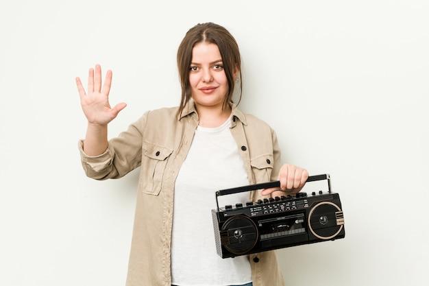 Junge curvy frau, die eine lächelnde nette darstellende nr. fünf des retro- radios mit den fingern hält.