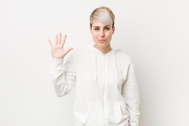 Junge curvy frau, die eine lächelnde nette darstellende nr. fünf des weißen hoodie mit den fingern trägt.