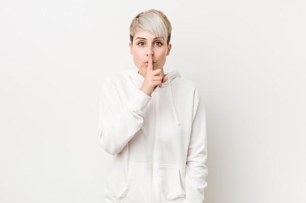 Junge curvy frau, die einen weißen hoodie hält ein geheimnis oder bittet um ruhe trägt.