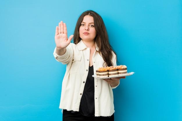 Junge curvy frau, halten die kleinen kuchen, die mit der ausgestreckten hand zeigt das stoppschild stehen und verhindern sie.