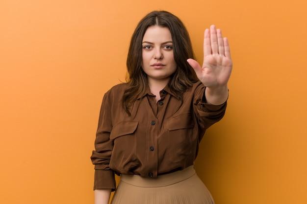 Junge curvy russische frau, die mit der ausgestreckten hand zeigt stoppschild steht