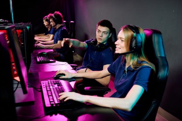 Junge cyber-sport-spieler, die mädchen in kopfhörern beraten, während sie sich auf den e-sport-wettbewerb vorbereiten