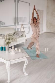 Junge dame beginnt morgens mit yoga-übungen im schlafzimmer